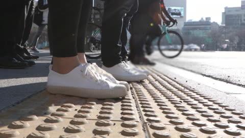 vídeos y material grabado en eventos de stock de the side view of the people's leg and walking on the crossroad in the city buildings - esfuerzo