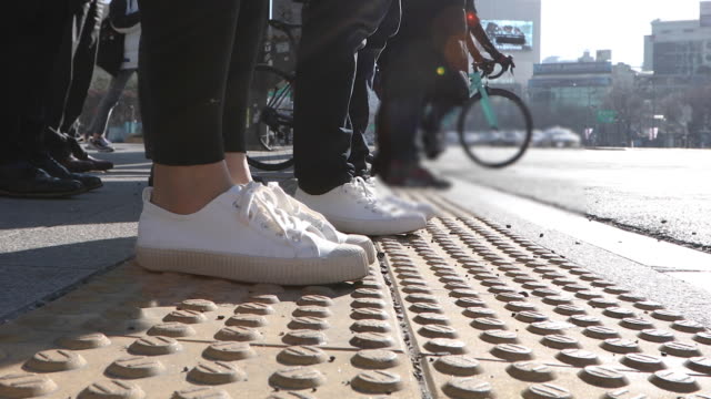 the side view of the people's leg and walking on the crossroad in the city buildings - footwear stock videos & royalty-free footage