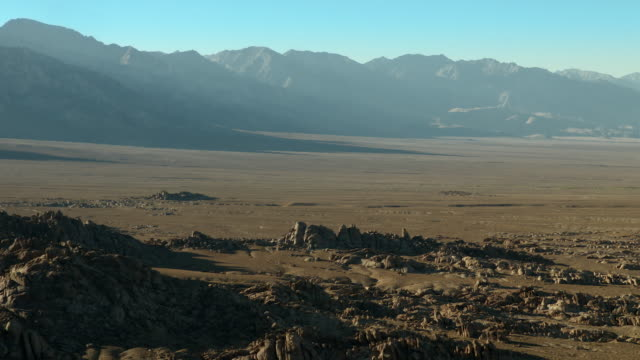 The Sierra escarpment provides a steep backdrop to the scattered rock formations of the Alabama Hills.