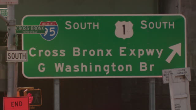 The sign for the cross bronx expressway to the george washington bridge towards I95 south and route 1 south in the bronx during the day as the tops of cars pass in front