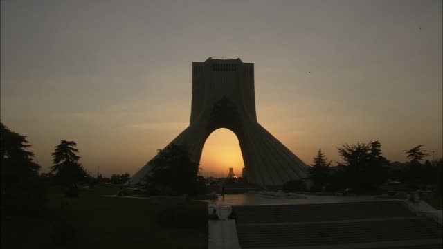 the silhouette of azadi tower is seen at golden hour. - tehran stock videos & royalty-free footage