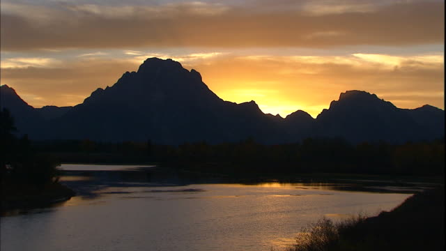the silhouette of mt. moran and oxbow bend contrasts against a bright orange sky. - mt moran stock videos & royalty-free footage