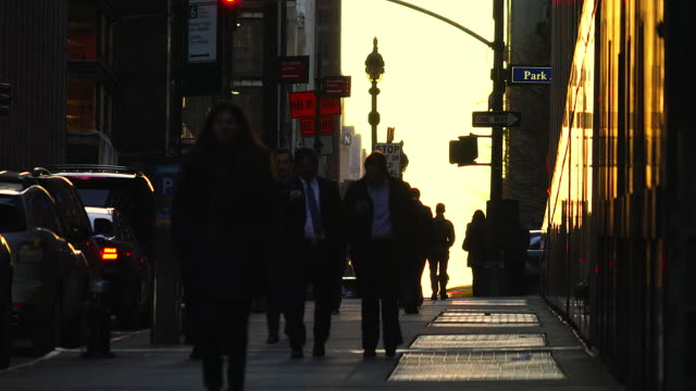 the silhouettes of commuters appear in the sunset glow sky during the evening commute time at midtown manhattan on mar. 29 7017. - segnale per macchine e pedoni video stock e b–roll