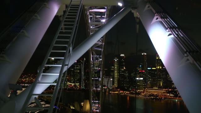 the singapore flyer operates at night as the marina bay sands hotel and casino, left, and commercial buildings in the the central business district... - ナイトイン点の映像素材/bロール