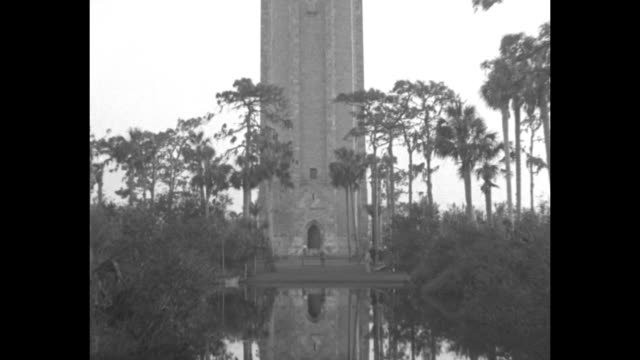 vidéos et rushes de the singing tower at bok tower gardens ; reflected tower in pool; vo birds; pan up tower, with american flag mounted on it fluttering in breeze / us... - choeur