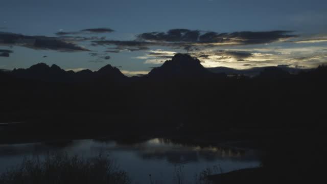 vídeos y material grabado en eventos de stock de the sky at sunset contrasts with the silhouetted teton range. - río snake
