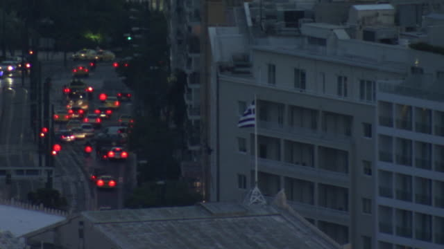 the 'sky blue-white' flag of greece flies above a building at twilight in athens, greece. - street name sign stock-videos und b-roll-filmmaterial