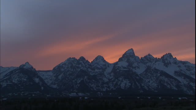 The sky glows behind the snowy Grand Teton Mountains.