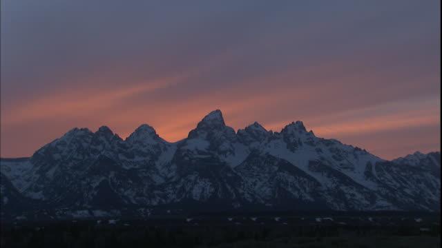 the sky glows behind the snowy grand teton mountains. - grand teton national park stock videos & royalty-free footage