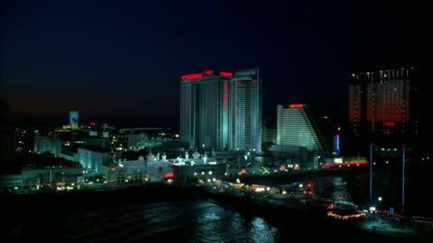 the sky glows red behind the trump taj mahal casino resort and the atlantic city boardwalk at night. - hd format stock-videos und b-roll-filmmaterial