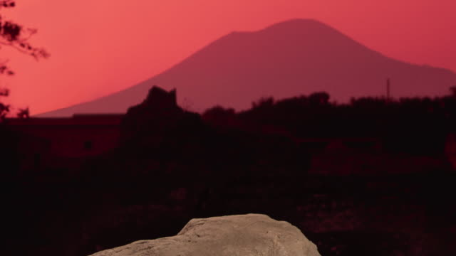 the sky glows red over mount vesuvius beyond a concrete cast of a pompeian victim in italy. - volcano stock videos & royalty-free footage