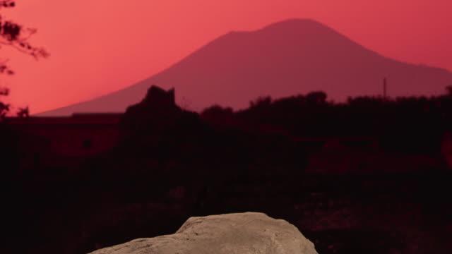 the sky glows red over mount vesuvius beyond a concrete cast of a pompeian victim in italy. - vulkan bildbanksvideor och videomaterial från bakom kulisserna