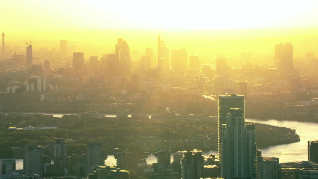 The sky glows yellow behind the London skyline.