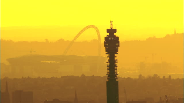 vídeos de stock e filmes b-roll de the sky glows yellow behind wembley stadium and bt tower in london, england. - bt tower londres