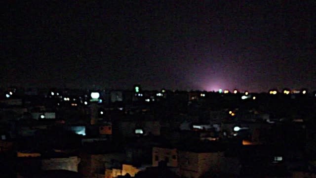 The sky lights up after a plane drops bombs at a target in Aleppo Syria