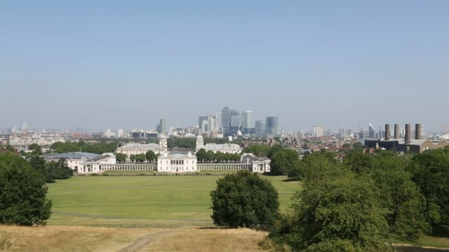The skyline of Londons Canary Wharf financial district is viewed from Greenwich park in London UK on Thursday July 24 Back view tourists in Greenwich...