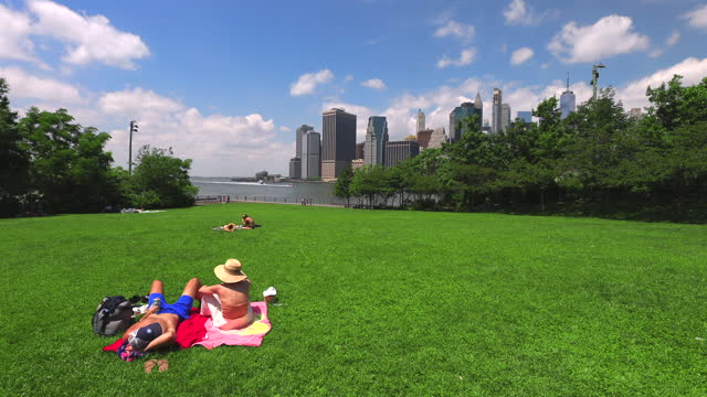 the skyline of manhattan stands in the distance as people sit on the lawn of brooklyn bridge park on june 20, 2021 in the brooklyn borough of new... - young couple stock videos & royalty-free footage