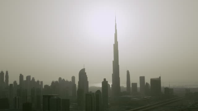 The skyscrapers of Downtown Dubai are silhouetted against a hazy sky.