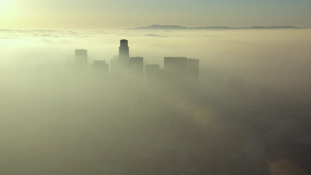 vídeos de stock, filmes e b-roll de the skyscrapers of downtown los angeles rise above a thick cover of fog stretching to the horizon. - ambiente dramático