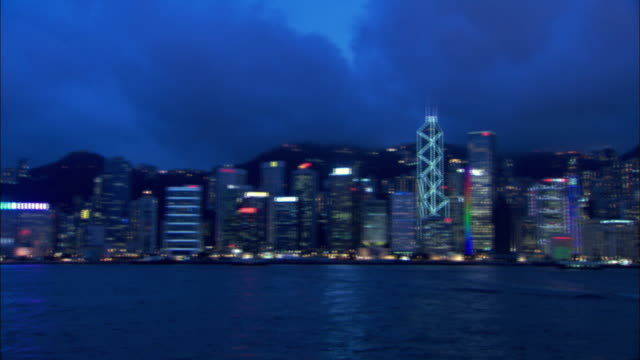 the skyscrapers of hong kong island light up a stormy evening sky. available in hd. - hsbc main building stock videos and b-roll footage
