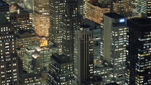 The skyscrapers of Manhattan glitter in the night sky.
