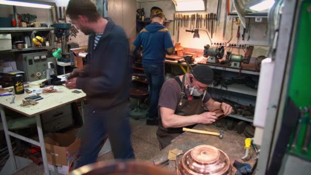 stockvideo's en b-roll-footage met het kleine team van de handarbeiders, ambachtslieden, werken in de kleine metalen winkel. - messing about