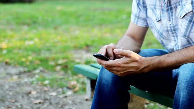 vídeos de stock e filmes b-roll de o telefone inteligente - banco de parque