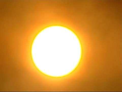 the smog infested city of linfen in china general view of brightly glowing sun as thin smoke drifts across it / thicker smoke drifting across - skadedjursangrepp bildbanksvideor och videomaterial från bakom kulisserna