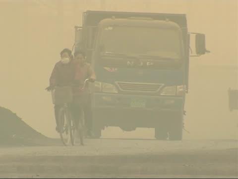 the smog infested city of linfen in china more of smoggy street several lorries pass by - skadedjursangrepp bildbanksvideor och videomaterial från bakom kulisserna