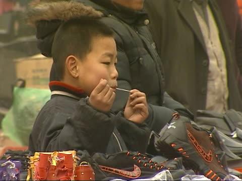 the smog infested city of linfen in china various of market traders stalls on street people looking at goods - skadedjursangrepp bildbanksvideor och videomaterial från bakom kulisserna
