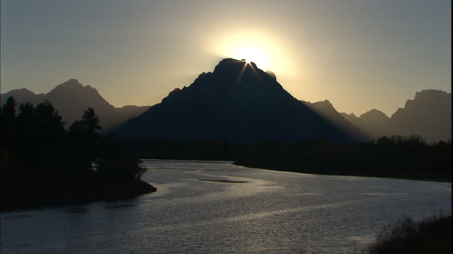 the snake river flows past a silhouetted mt. moran at golden hour. - mt moran stock videos & royalty-free footage