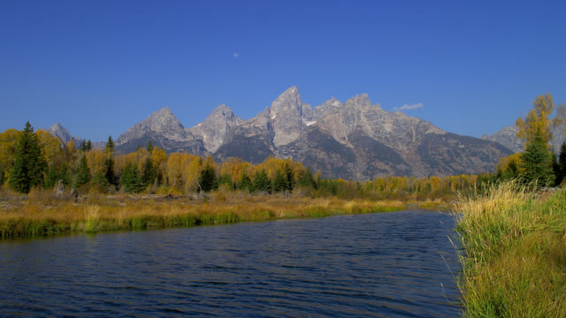 The Snake River flows past Schwabacher's Landing at the foot of the majestic Grand Teton mountains.