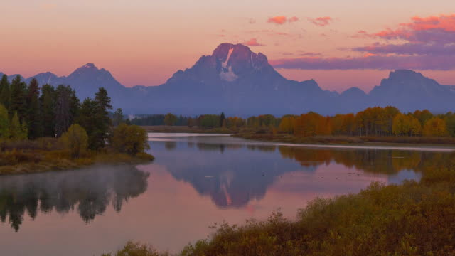 The Snake River reflects passing clouds and the Grand Teton mountains in Grand Teton National Park.
