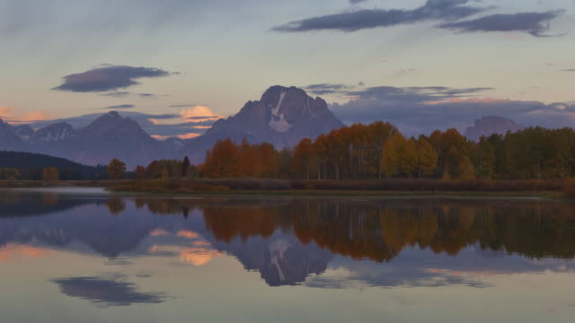 the snake river reflects the grand teton mountains and passing clouds in grand teton national park. - snake river stock videos and b-roll footage