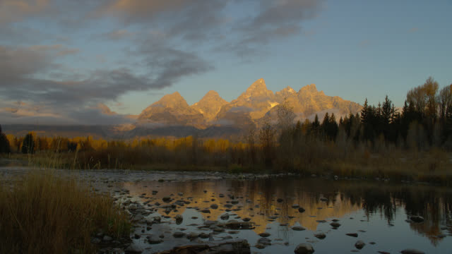 stockvideo's en b-roll-footage met the snake river reflects the wooded banks of schwabacher's landing and the grand teton mountains in the early morning. - snake river