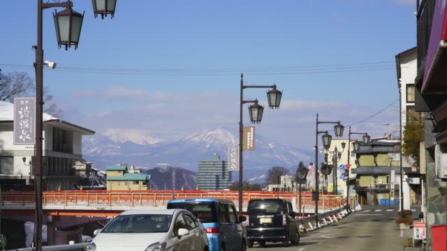 the snow covered mountains soar behind the street between the yokoyu river and houses at shibu onsen (shibu hot spring) yamanouchi-machi, nagano japan on feb. 17 2019. - nagano prefecture stock videos and b-roll footage