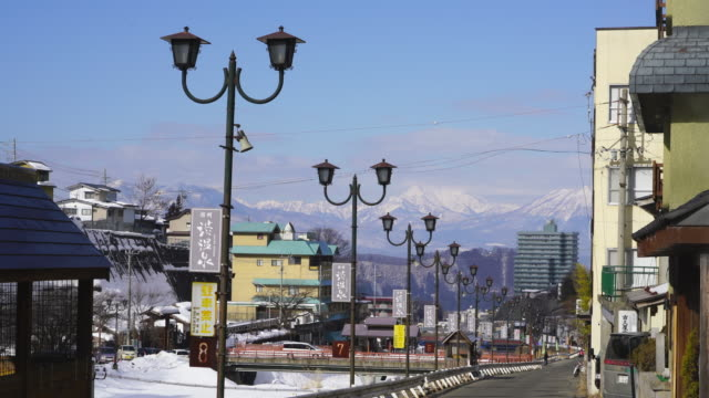 the snow covered mountains soar behind the street between the yokoyu river and houses at shibu onsen (shibu hot spring) yamanouchi-machi, nagano japan on feb. 17 2019. - jigokudani monkey park stock videos & royalty-free footage