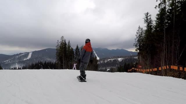 Die Snowboarder senkt sich die Skipiste hinunter.