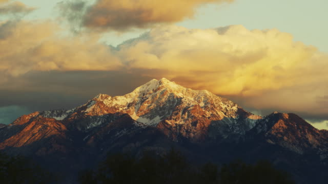 the snowcapped wasatch mountains above salt lake city, ut at sunrise/sunset with a dramatic cloudscape - mountain range stock videos & royalty-free footage