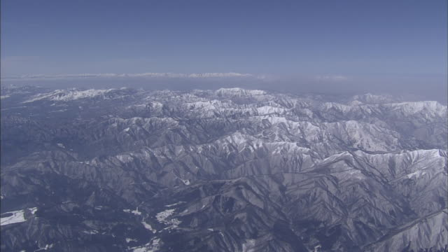 The snowy Tanigawa Mountain Range surrounds the distant Sea of Japan.