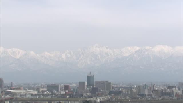 the snowy tateyama mountain range borders toyama city, japan. - toyama prefecture stock videos and b-roll footage