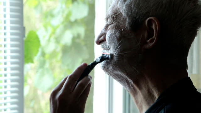 the son's hand shaves the stubble on his father's face. - stubble stock videos & royalty-free footage
