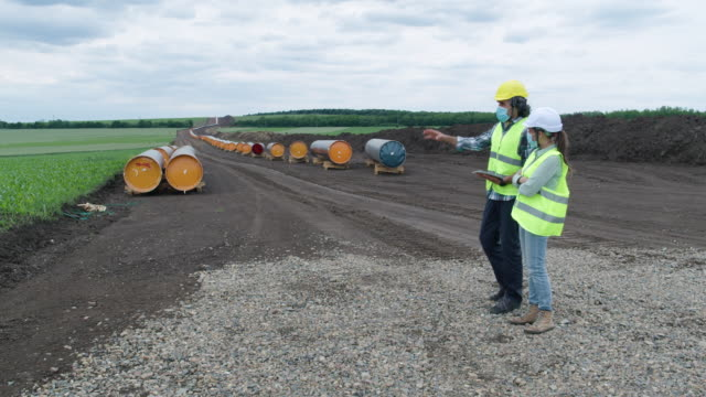 the south stream pipeline lng oil gas equipment. oil and gas engineers at refinery industry working on the field at a construction site of a natural gas plant. teamwork  during the covid-19 pandemic. - stereotypically working class stock videos & royalty-free footage