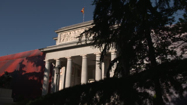 vídeos de stock e filmes b-roll de the spanish flag waving in the wind in slow motion on top of the prado museum façade, madrid, spain - prado