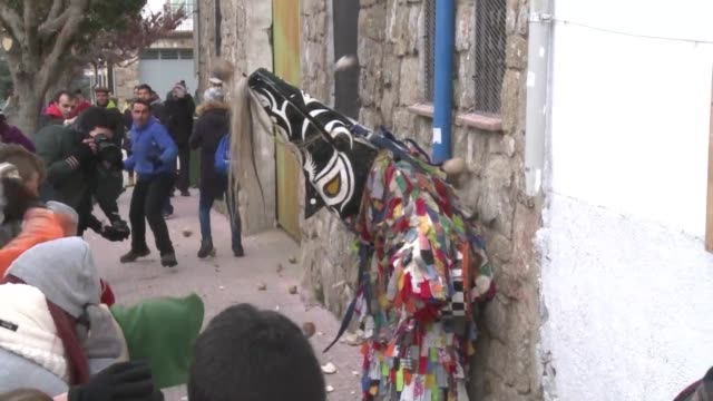 vídeos de stock, filmes e b-roll de the spanish village of piornal welcomes in the new year on saint sebastian day with a novel tradition pelting a man dressed up as a devil with... - crucifers
