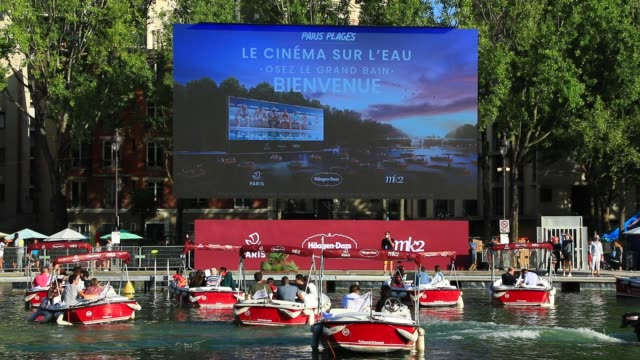 """the spectators prepare to watch the film on boats during paris plages launch of """"le cinema sur l'eau"""" with the screening of """"le grand bain"""" at bassin... - laziness stock videos & royalty-free footage"""