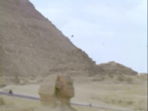 vídeos de stock e filmes b-roll de pan the sphinx and great pyramid / giza, egypt - 1960