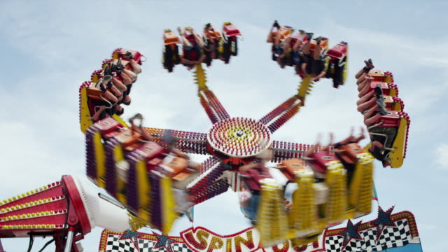 the spin out attraction ride twirls wildly on the midway at a state fair. - nebraska stock-videos und b-roll-filmmaterial