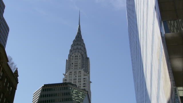 the spire of the chrysler building towers over adjacent high-rises. - chrysler building stock videos & royalty-free footage
