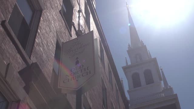 the spire of the old north church in boston stretches up to the blue sky behind a banner. - old north church stock videos & royalty-free footage